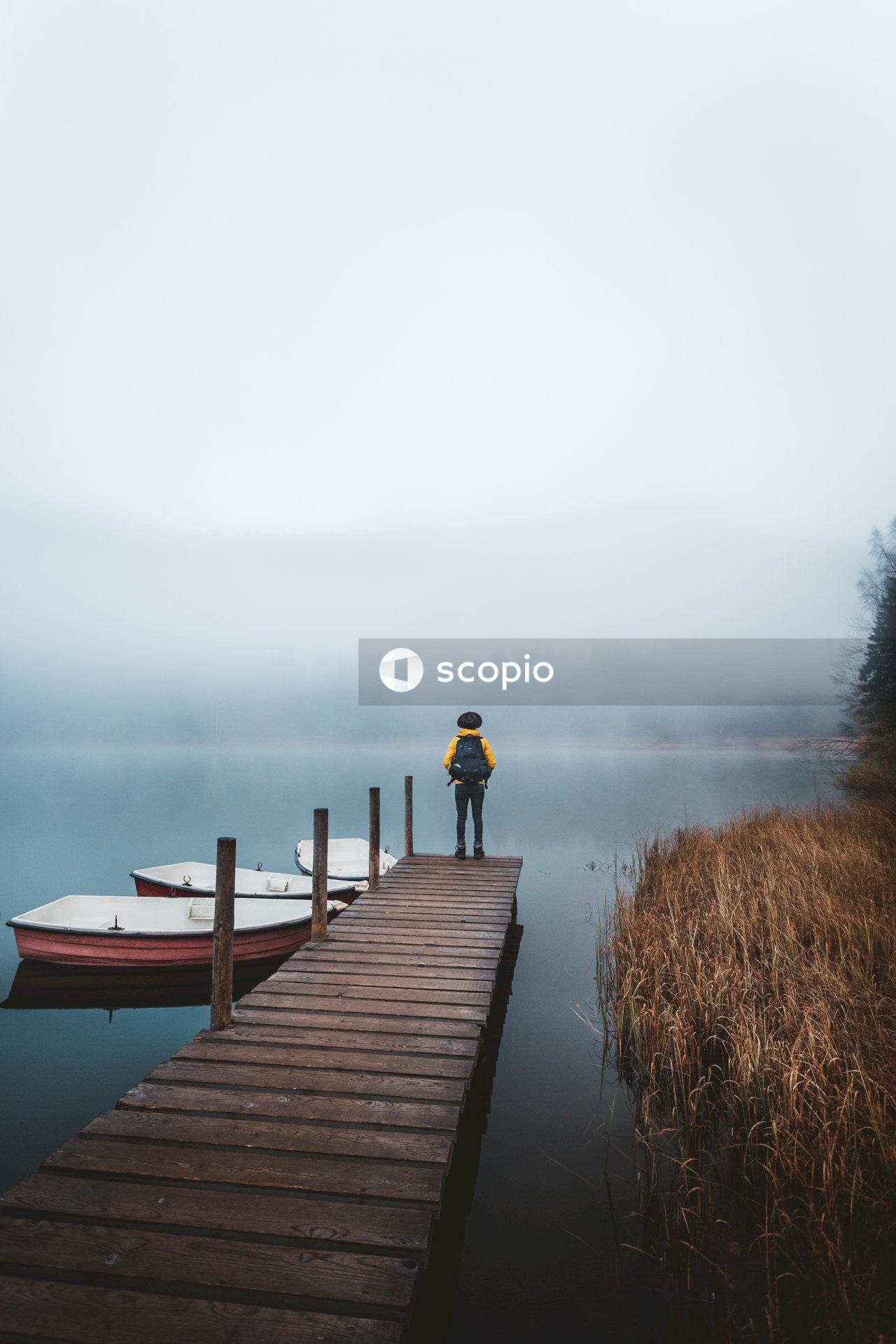 Person in black jacket and black pants standing on brown wooden dock