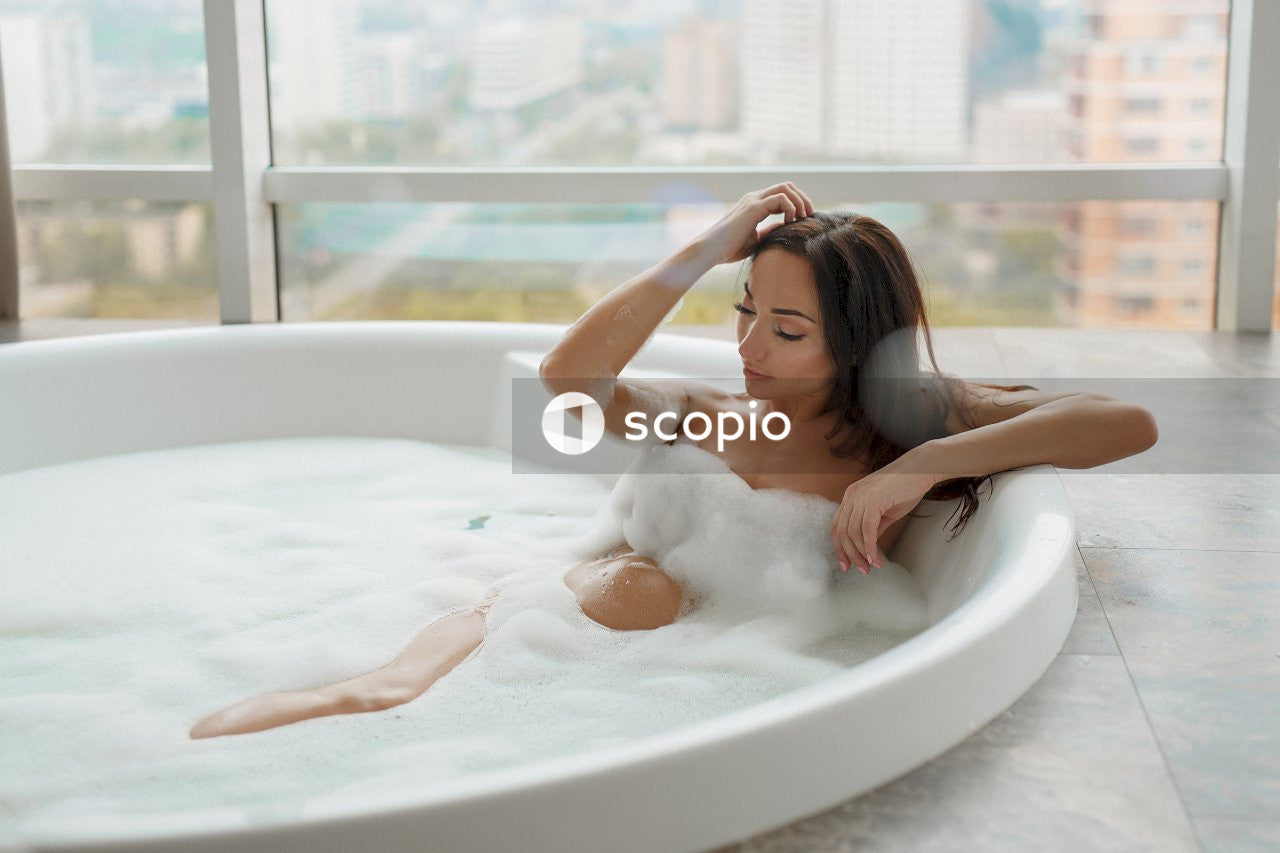 Woman on bathtub holding hair