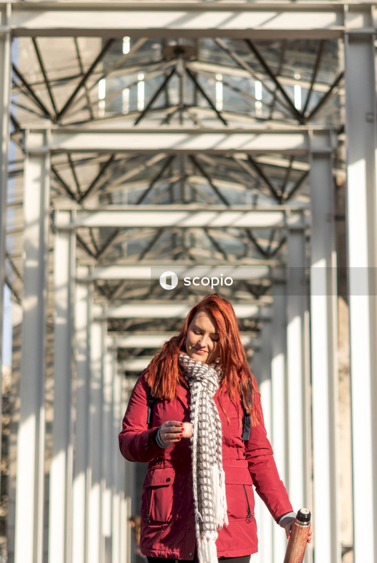 Woman in red jacket standing near white metal bridge
