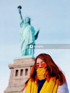 Woman in orange scarf and black sunglasses standing near statue of liberty