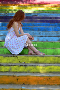 Woman wearing white dress sitting on stairs