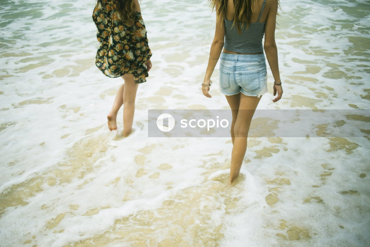 Two women standing on sea at daytime