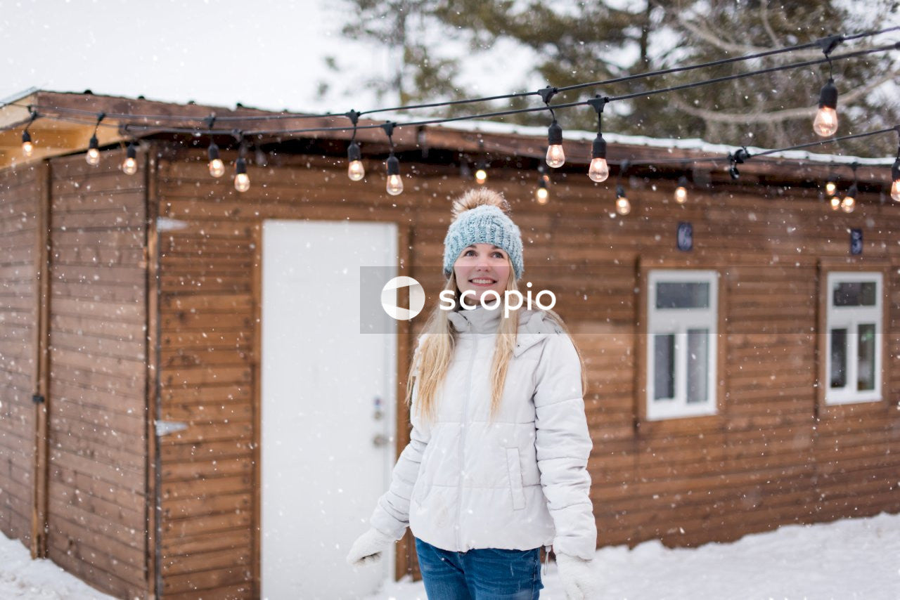 Woman in white long sleeve shirt and blue denim jeans standing on snow covered ground