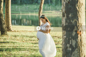 Pregnant woman in white dress standing by the tree near lake
