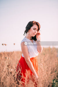 Woman standing on brown tall grass