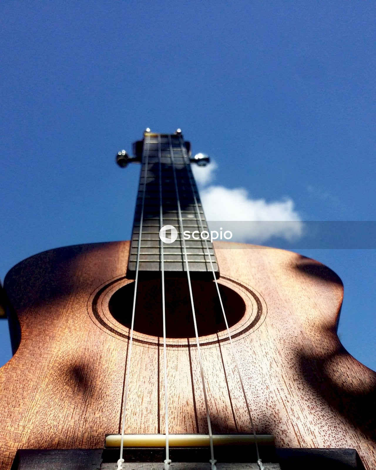 Brown acoustic guitar under blue sky