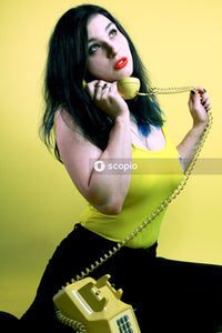 Woman wearing green tank top holding green telephone
