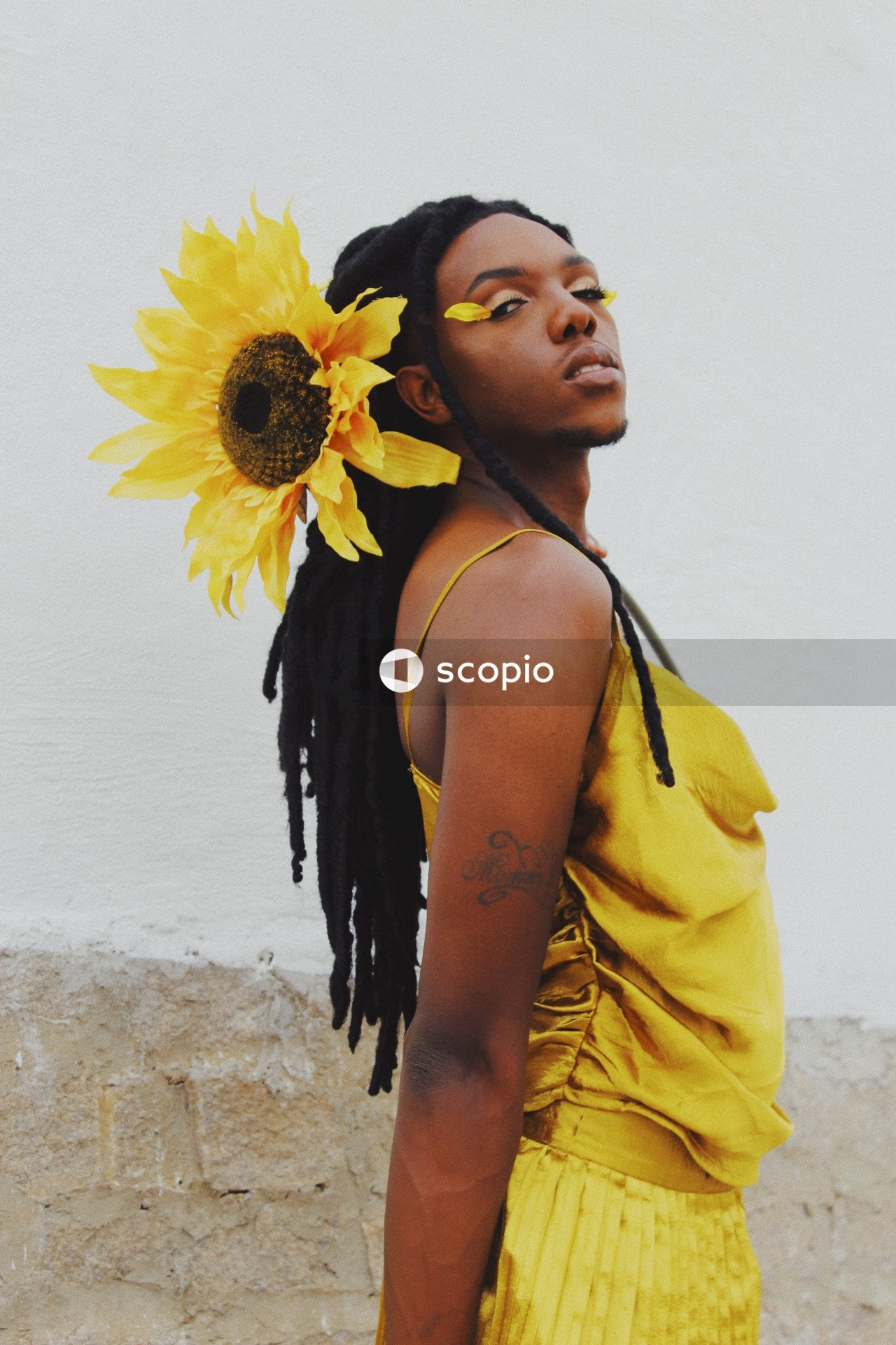 Man with makeup and in yellow dress and a sunflower in their dreadlocks