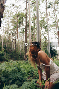 Woman in white tank top standing in forest