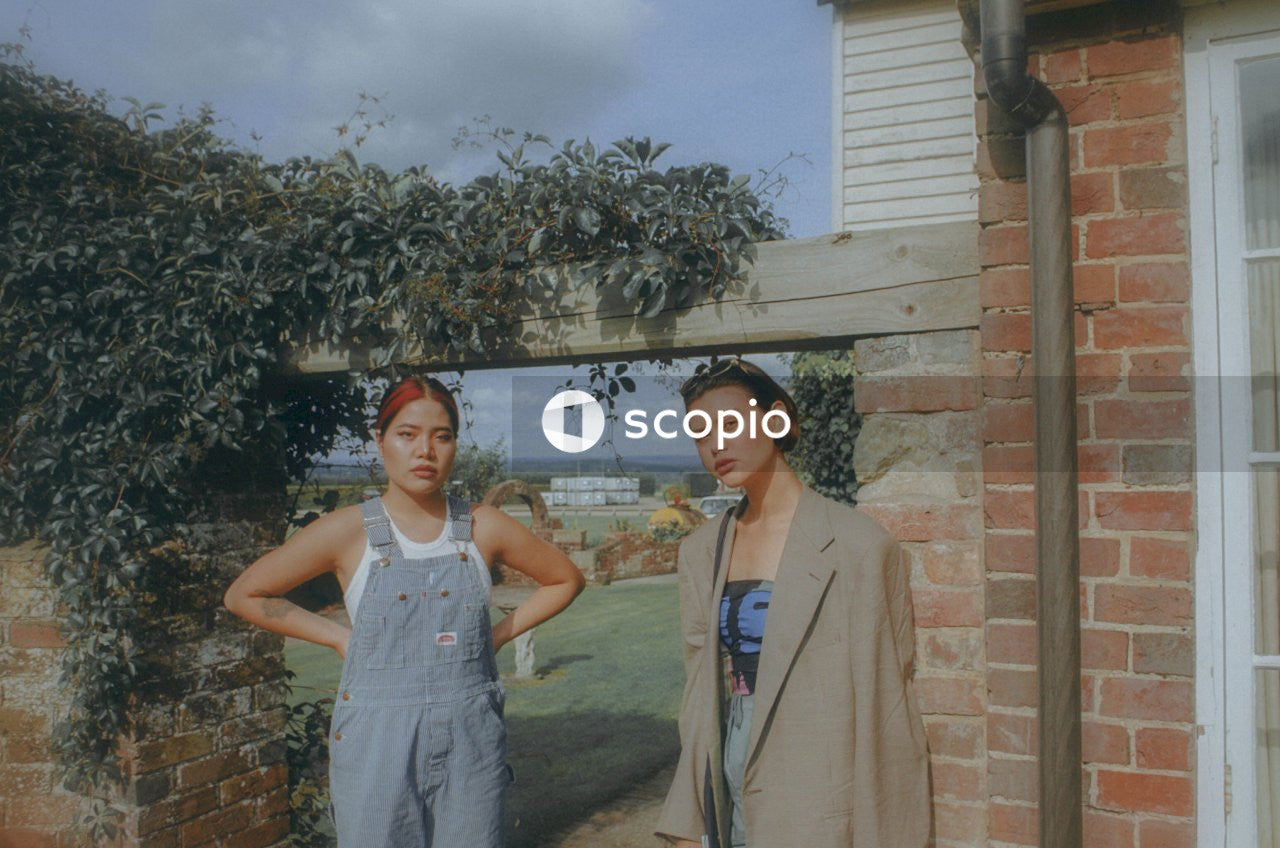 Two women standing beside house