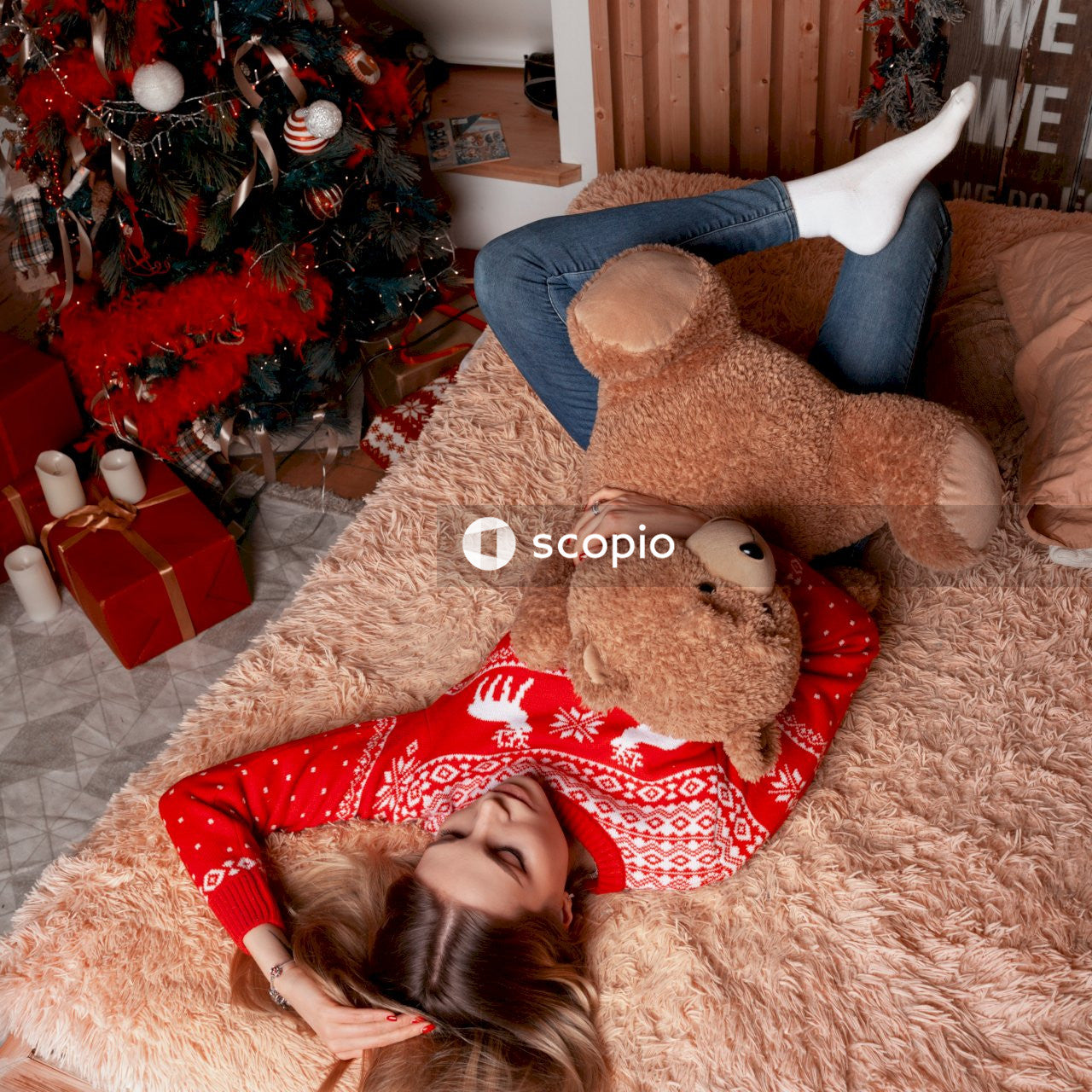 Woman lying on bed with bear plush toy