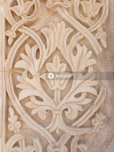 White floral carved on gray concrete wall