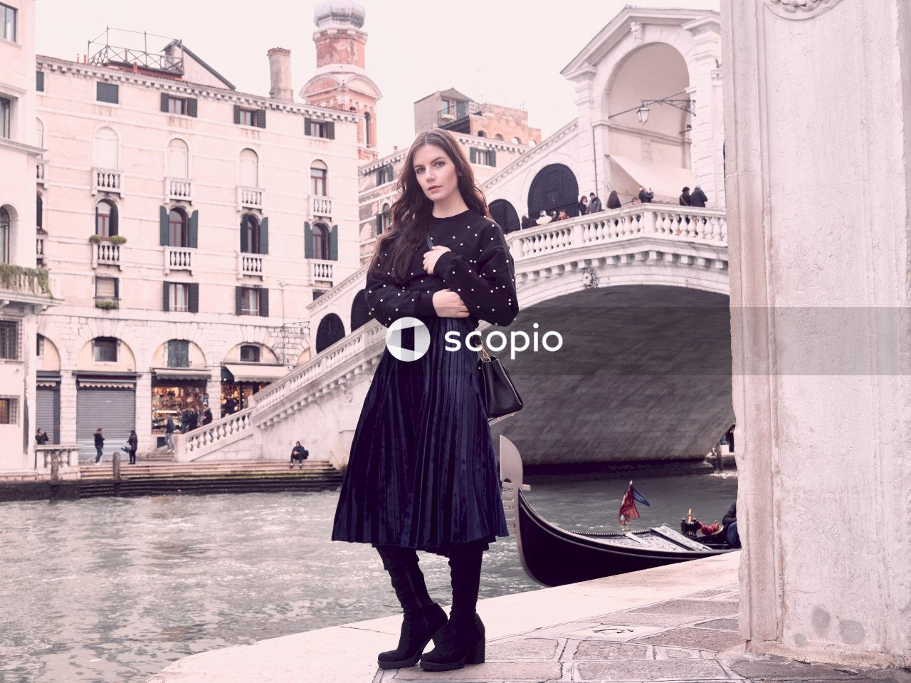 Woman wearing black long-sleeved dress standing in front of bridge