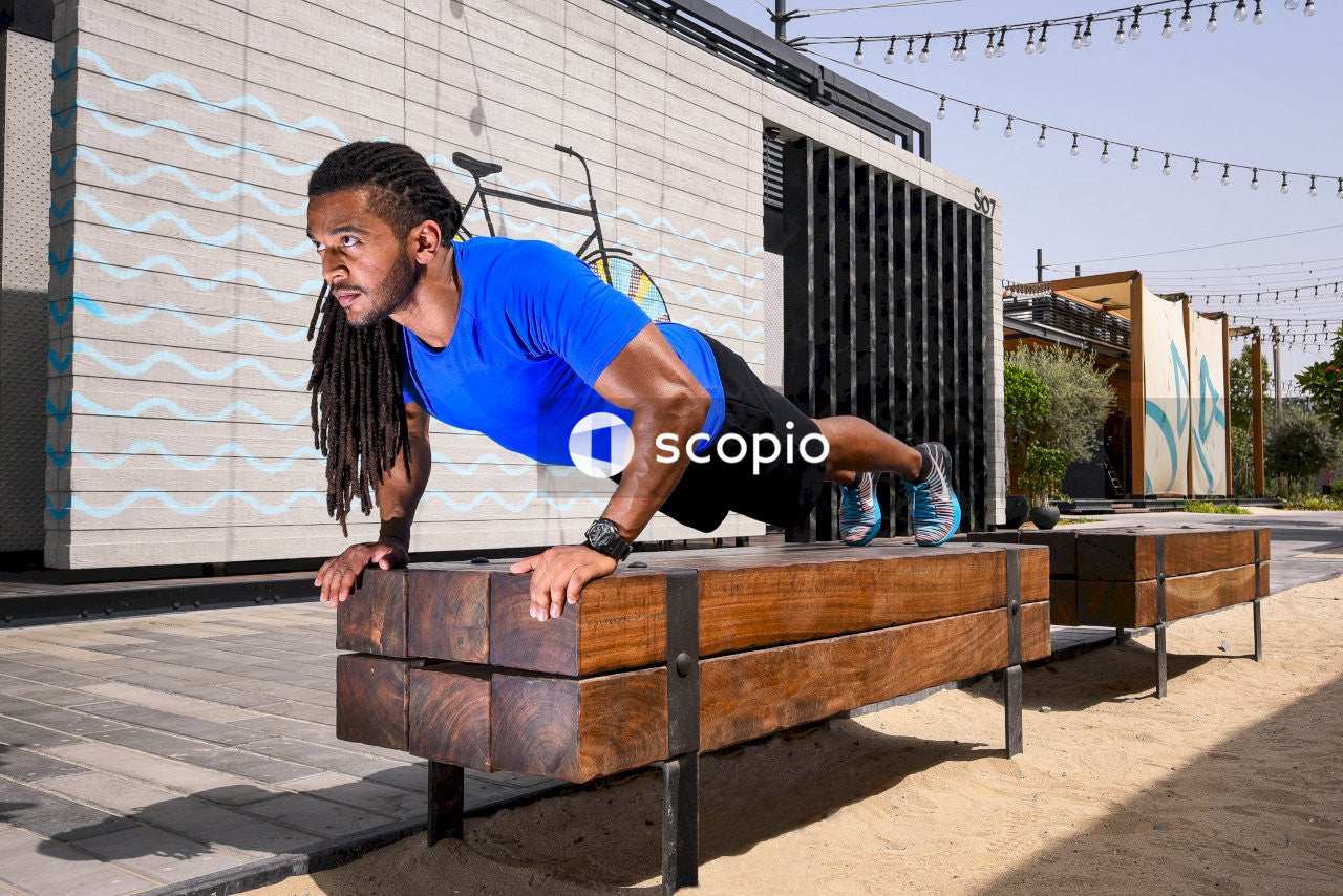 Man taking push up on wooden bench at daytime