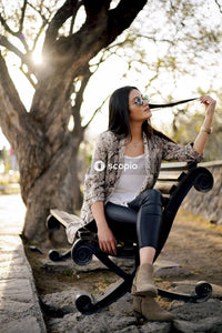 Woman in white lace long sleeve shirt sitting on black bench