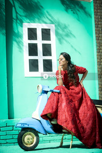 Stylish woman in long red dress sitting on motor scooter