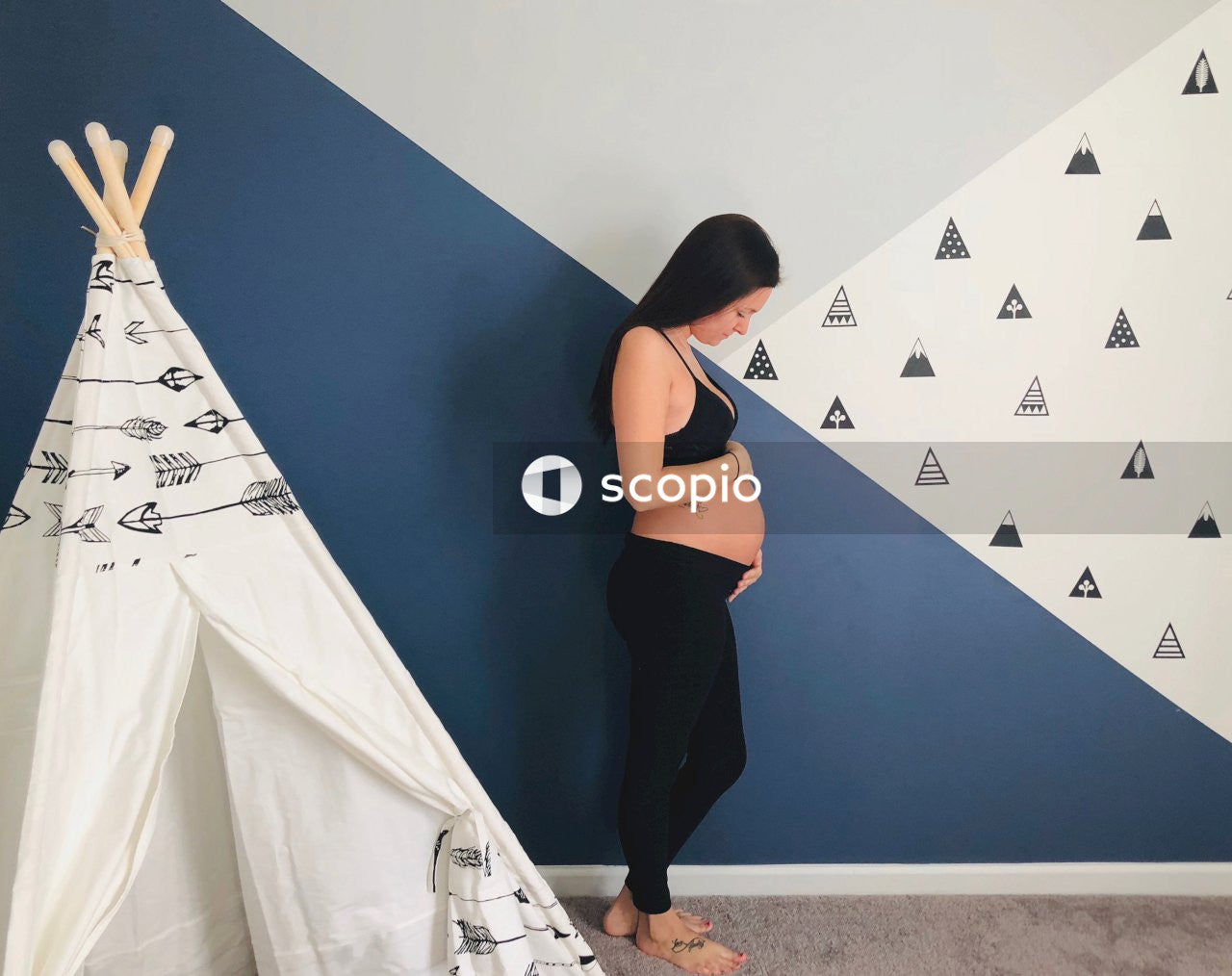 Pregnant woman touching her tummy while standing and facing her left side inside room near tipi tent