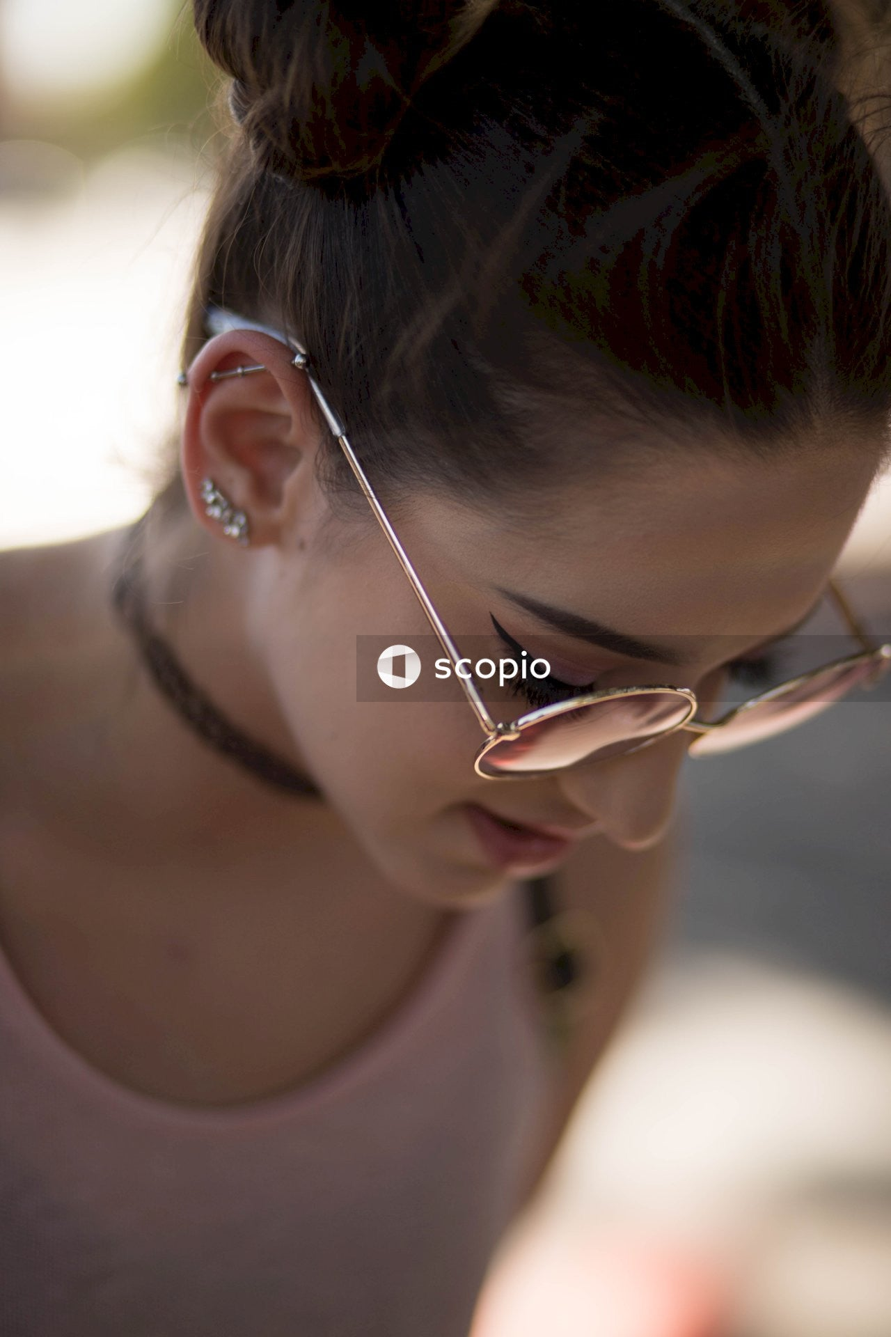 Woman wearing round sunglasses staring down