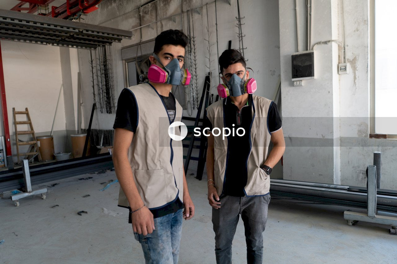 Two workers in gas masks at a steel factory