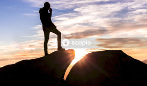 Silhouette of man standing on rocky hill during sunset