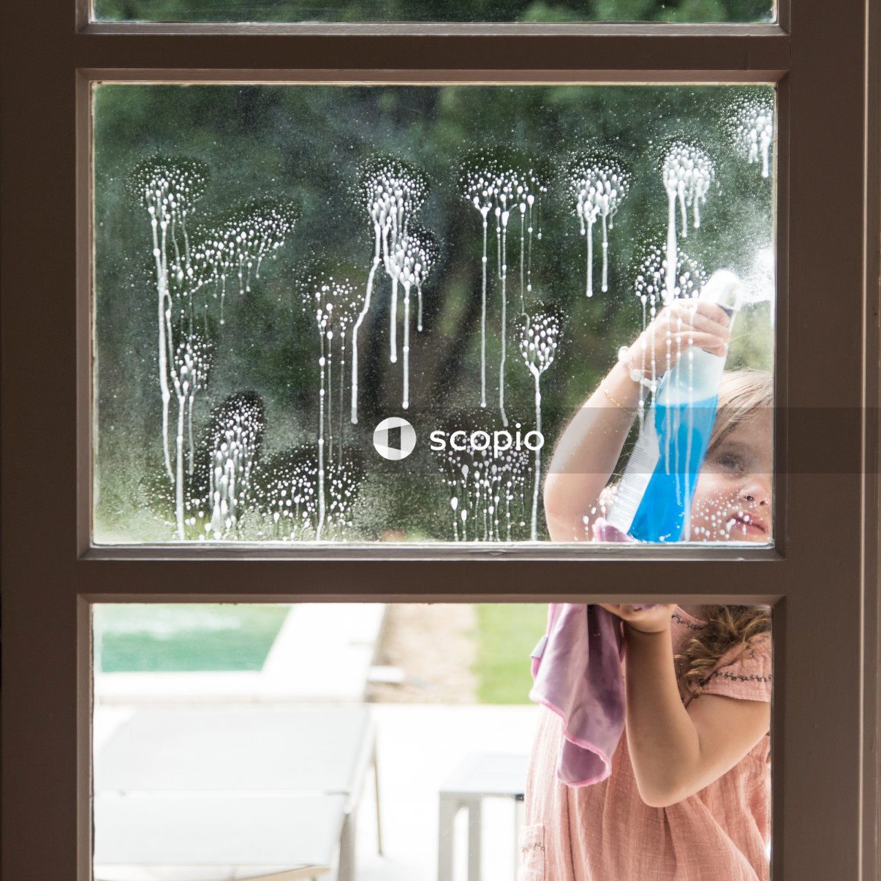 Girl spraying on window