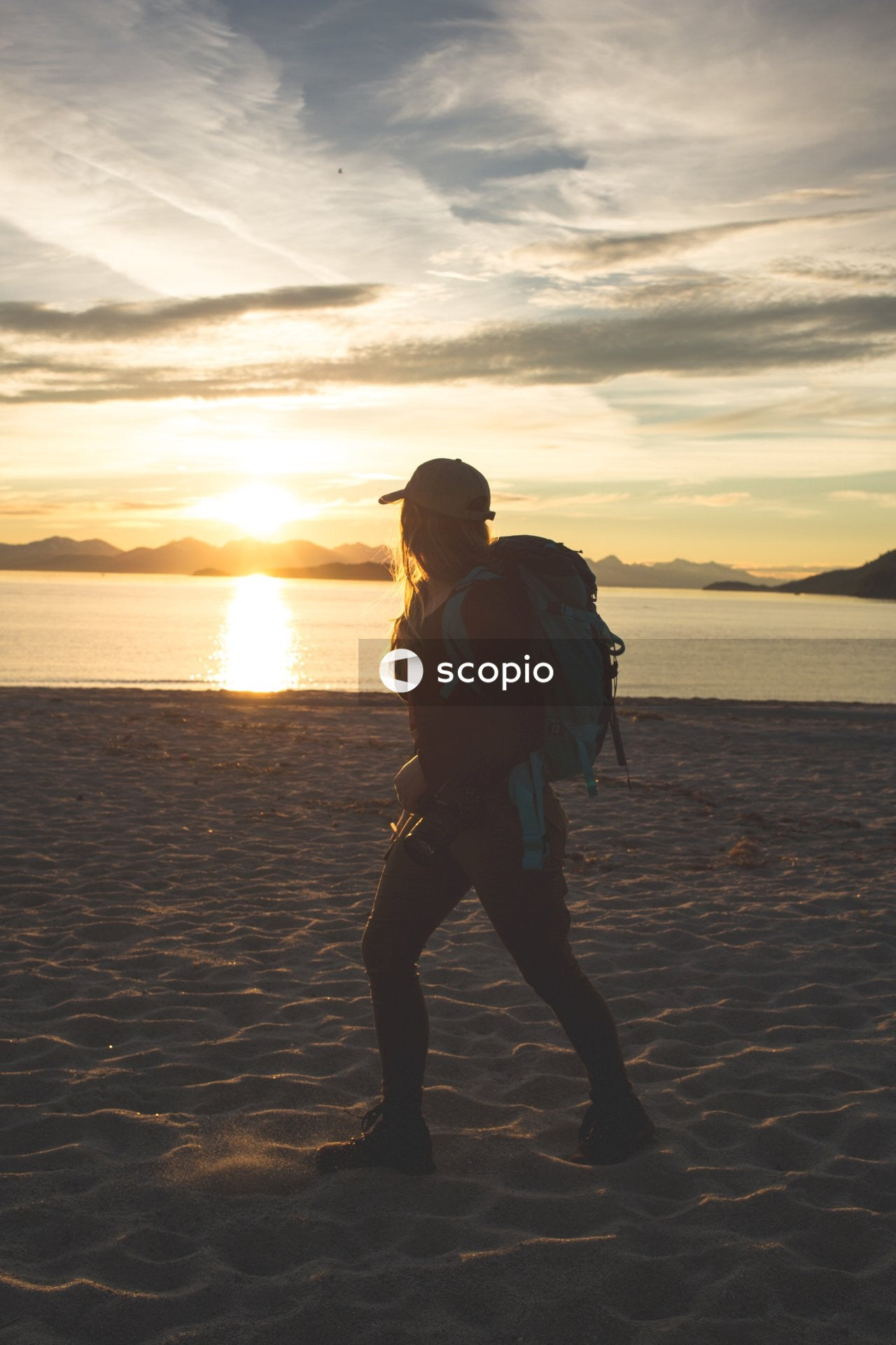 Man in black jacket and black pants standing on beach during sunset