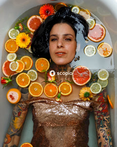 Portrait of woman surrounded by slices of fruit in bathtub
