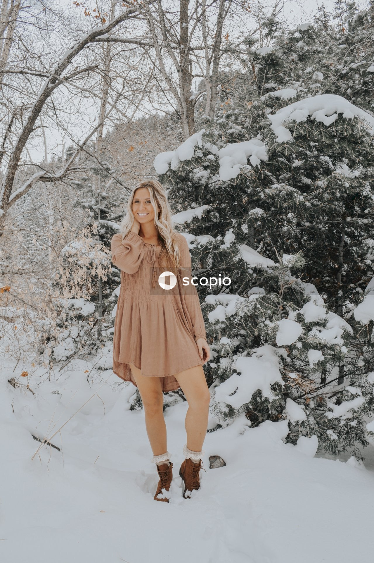 Woman in brown long sleeve dress standing on snow covered ground