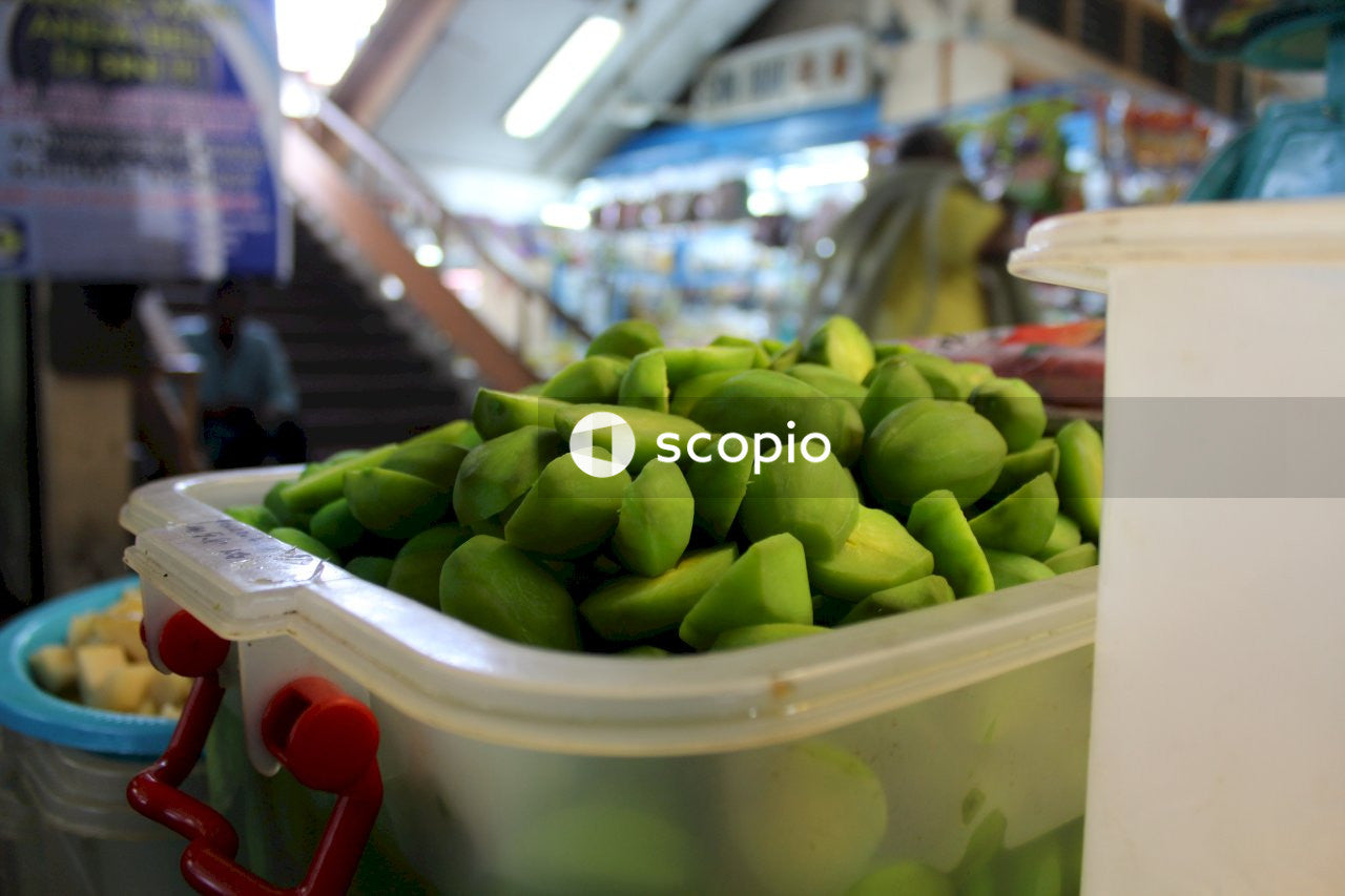 Green fruits in white plastic container