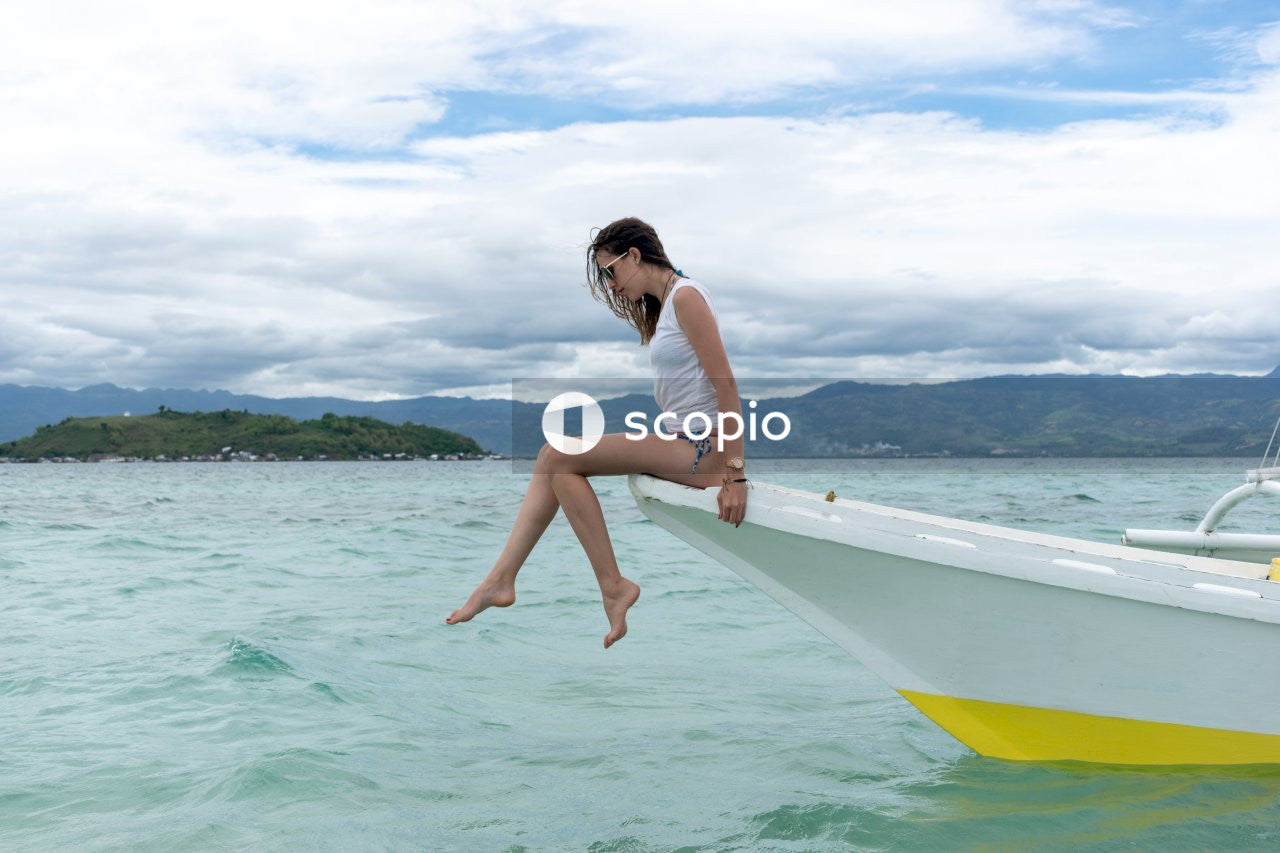 Woman in white tank top sitting on white surfboard on sea