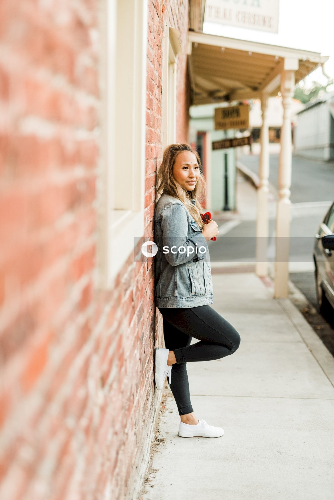 Woman in gray long sleeve shirt and black pants leaning on red brick wall