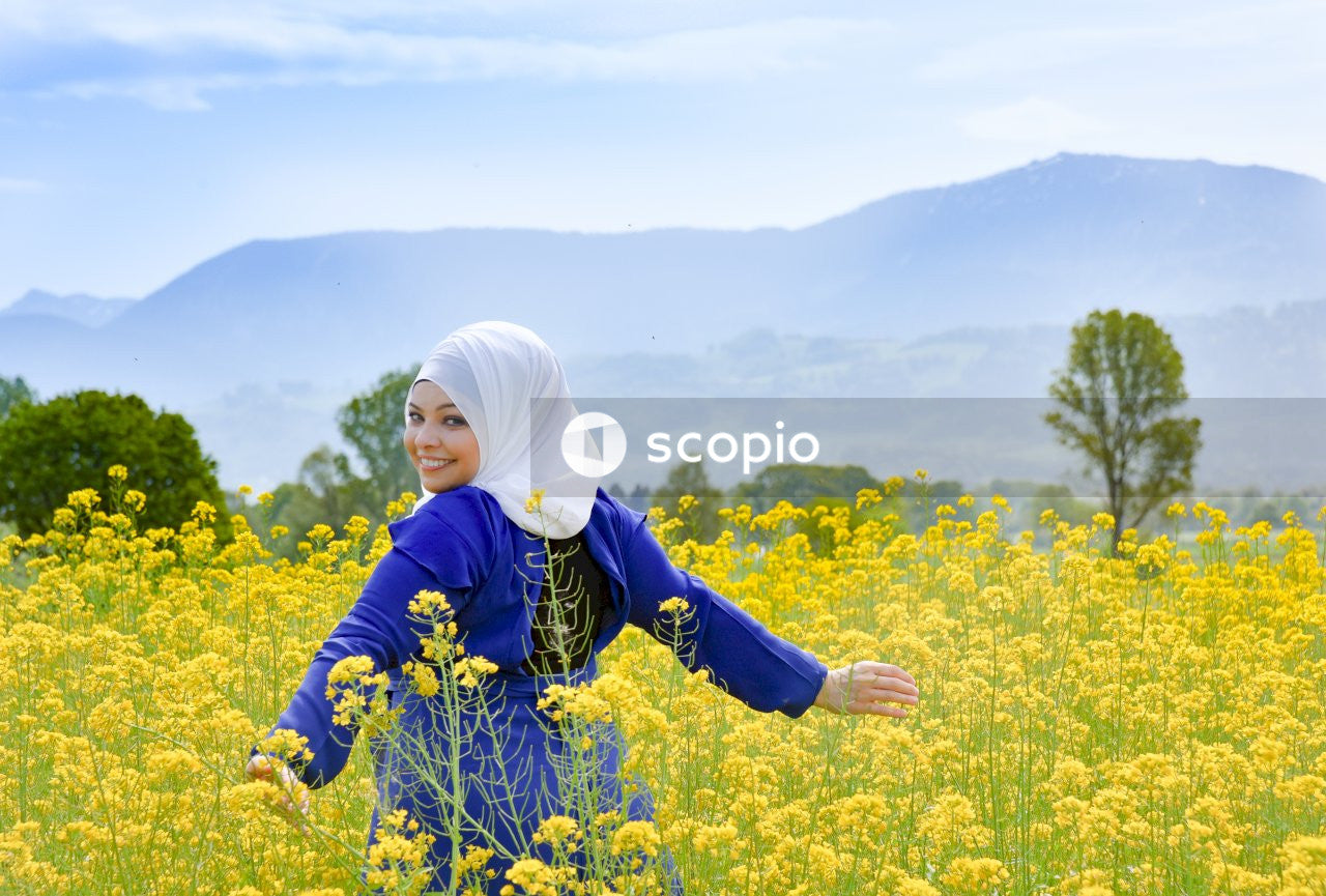 Woman in blue jacket standing on yellow flower field