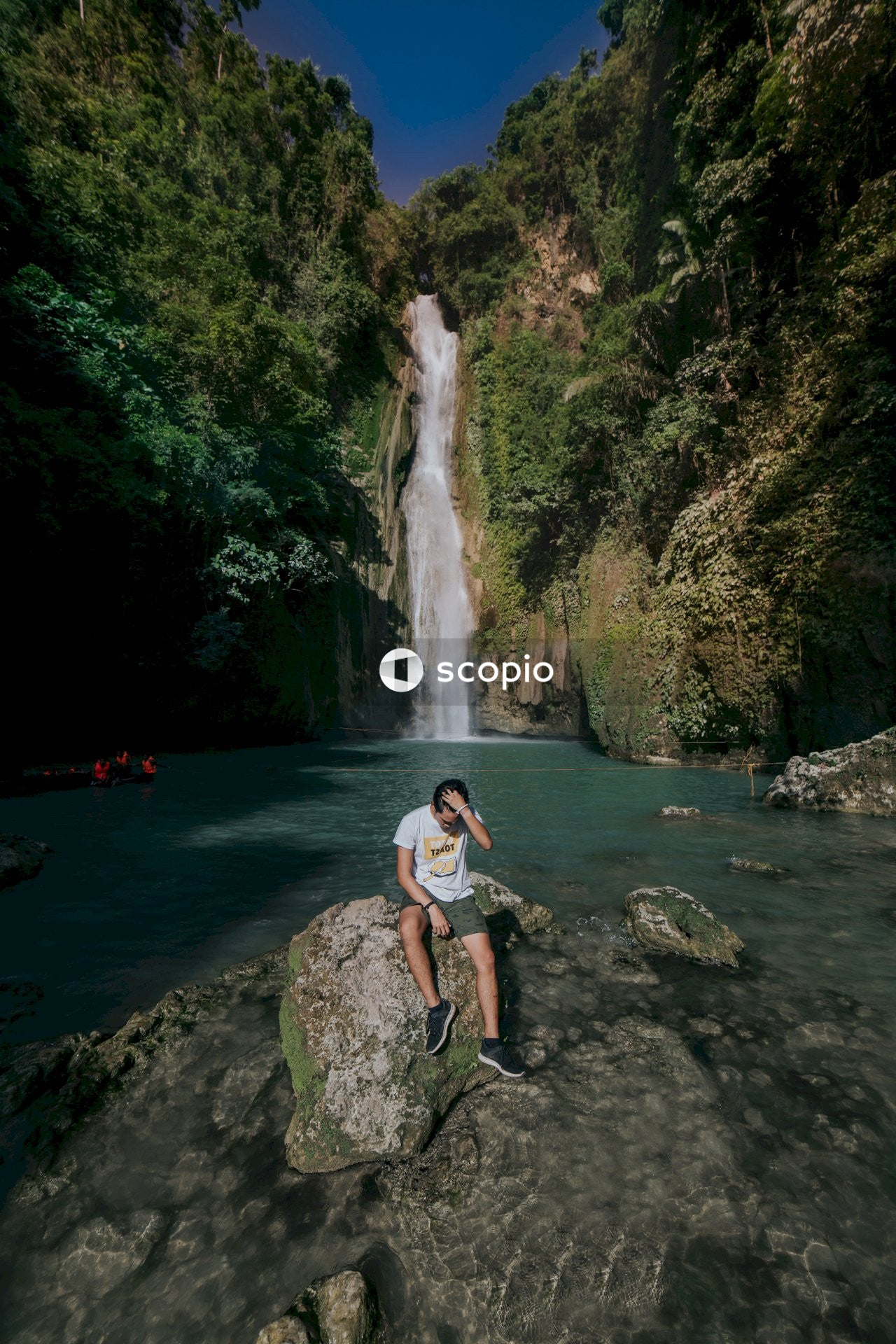 Woman in white tank top and black shorts sitting on rock near waterfalls