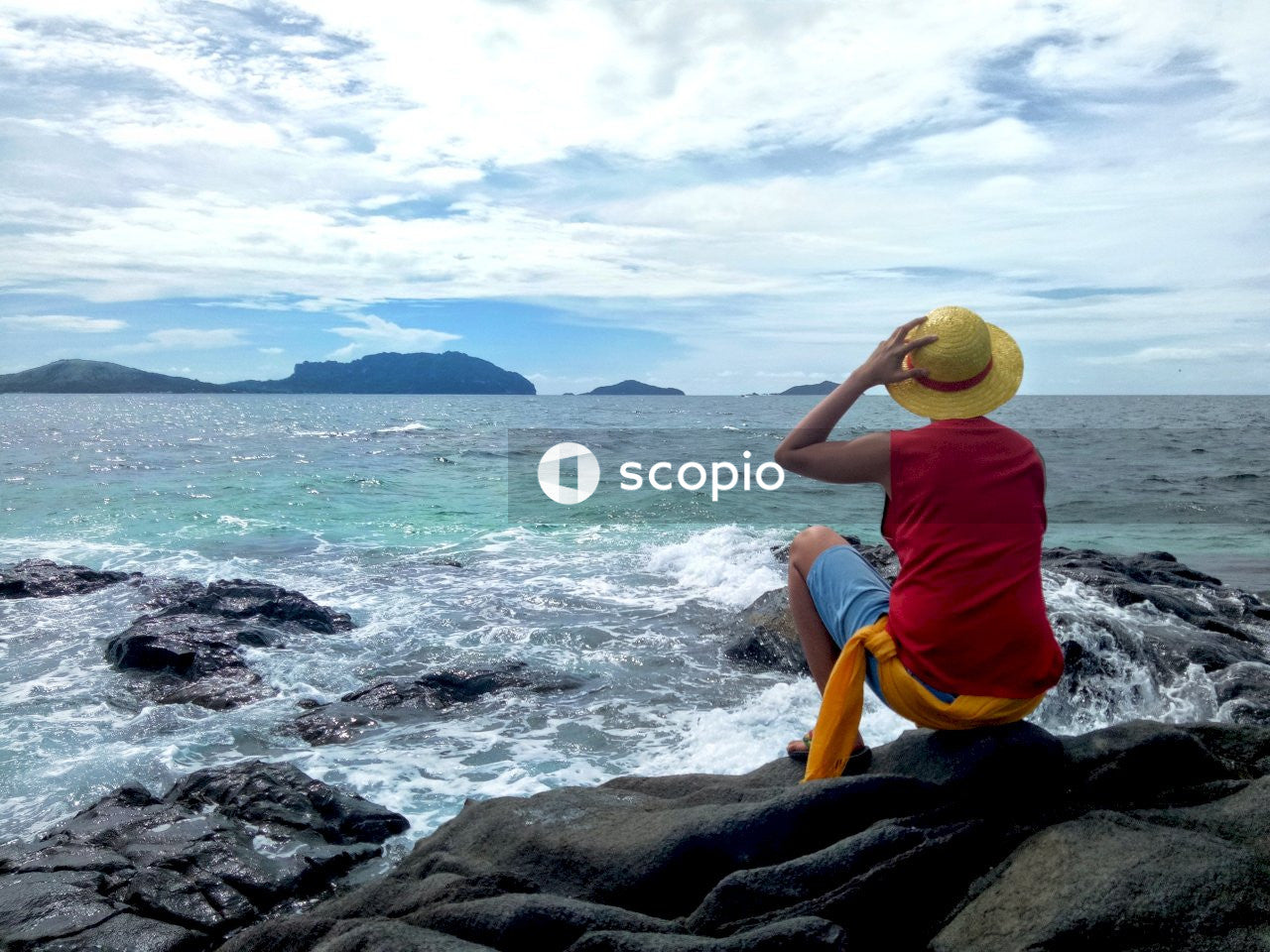 Man sitting on rock facing the sea