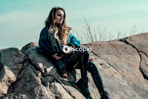 Woman in blue jacket and black pants sitting on rock