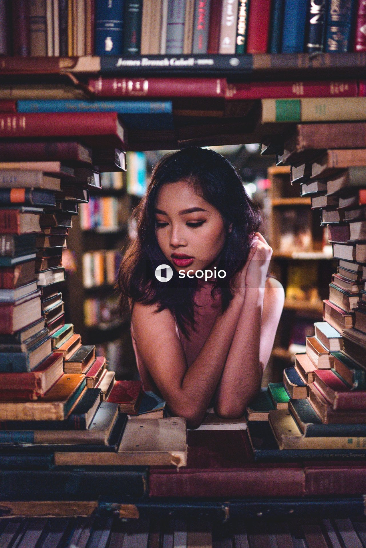 Shallow focus photo of woman near books