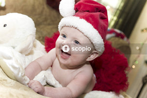 Baby in red and white santa hat lying on white fur textile