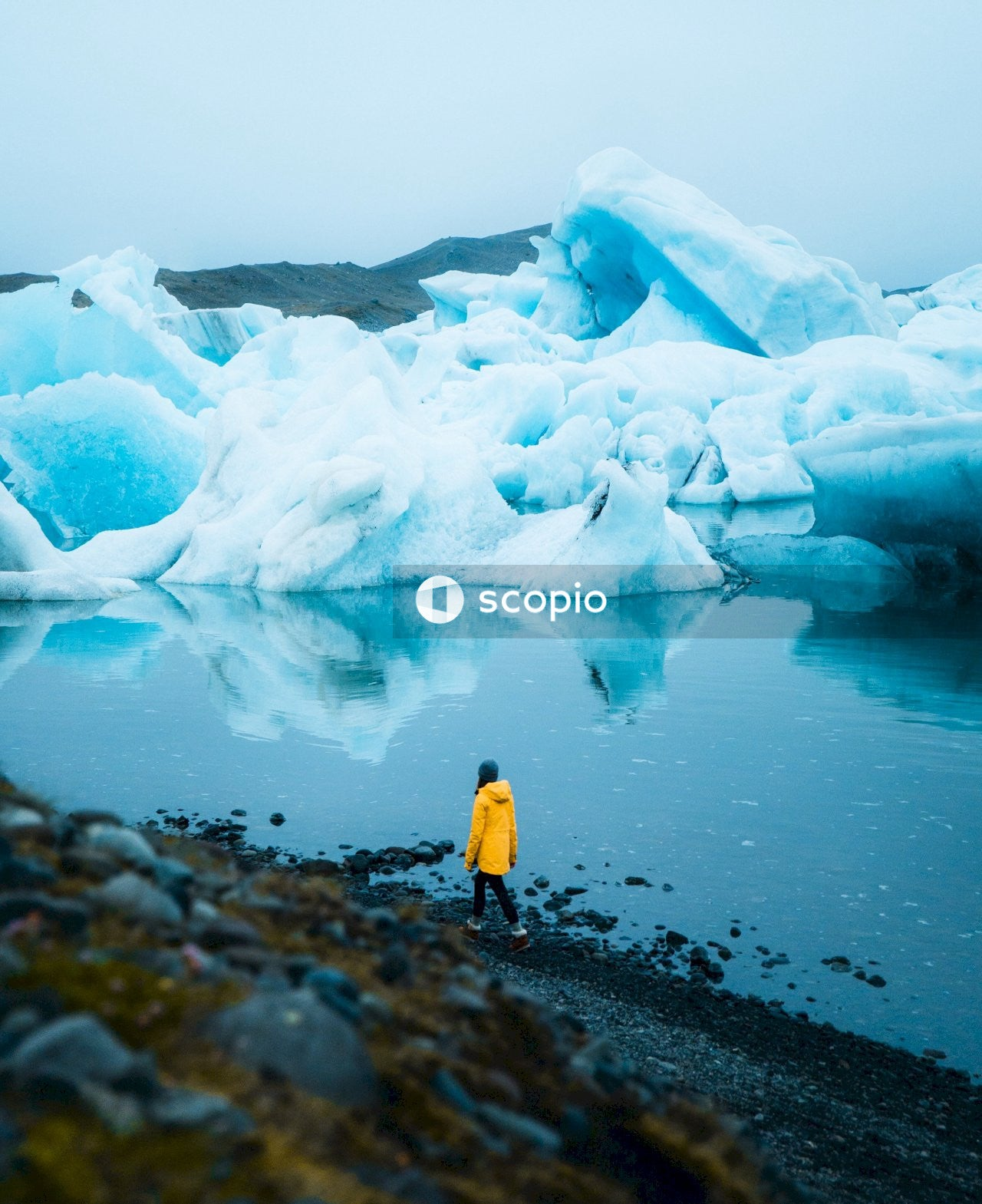Person in yellow jacket standing on rock near ice formation