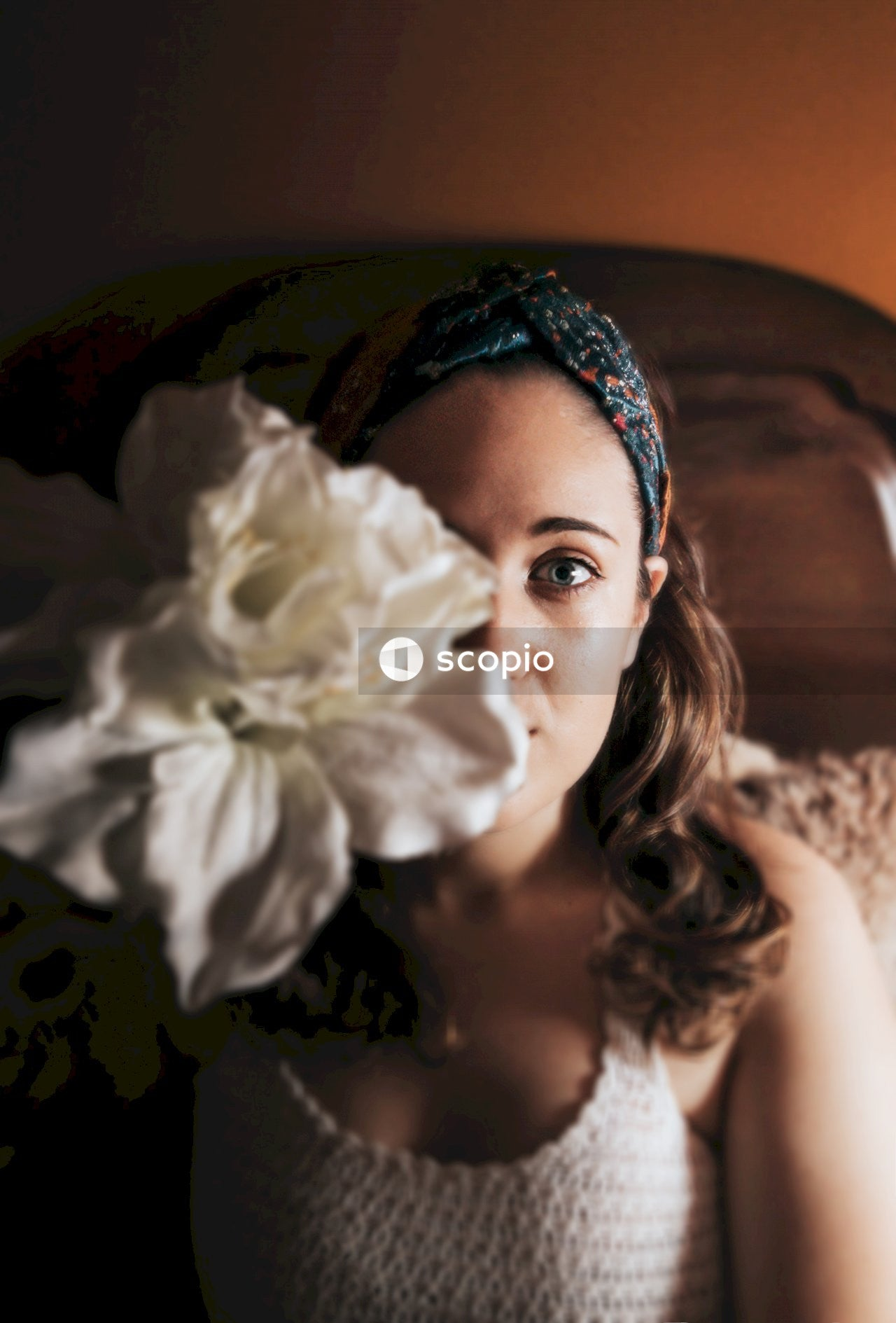 Woman in white floral dress with blue and white floral headdress