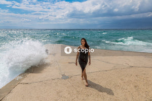 Woman in black spaghetti strap dress standing on beach