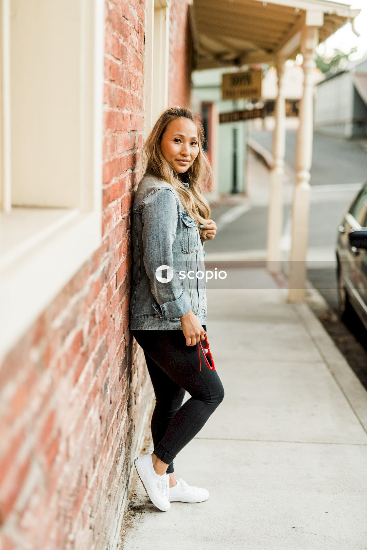 Woman in blue denim jacket and black pants leaning on red brick wall