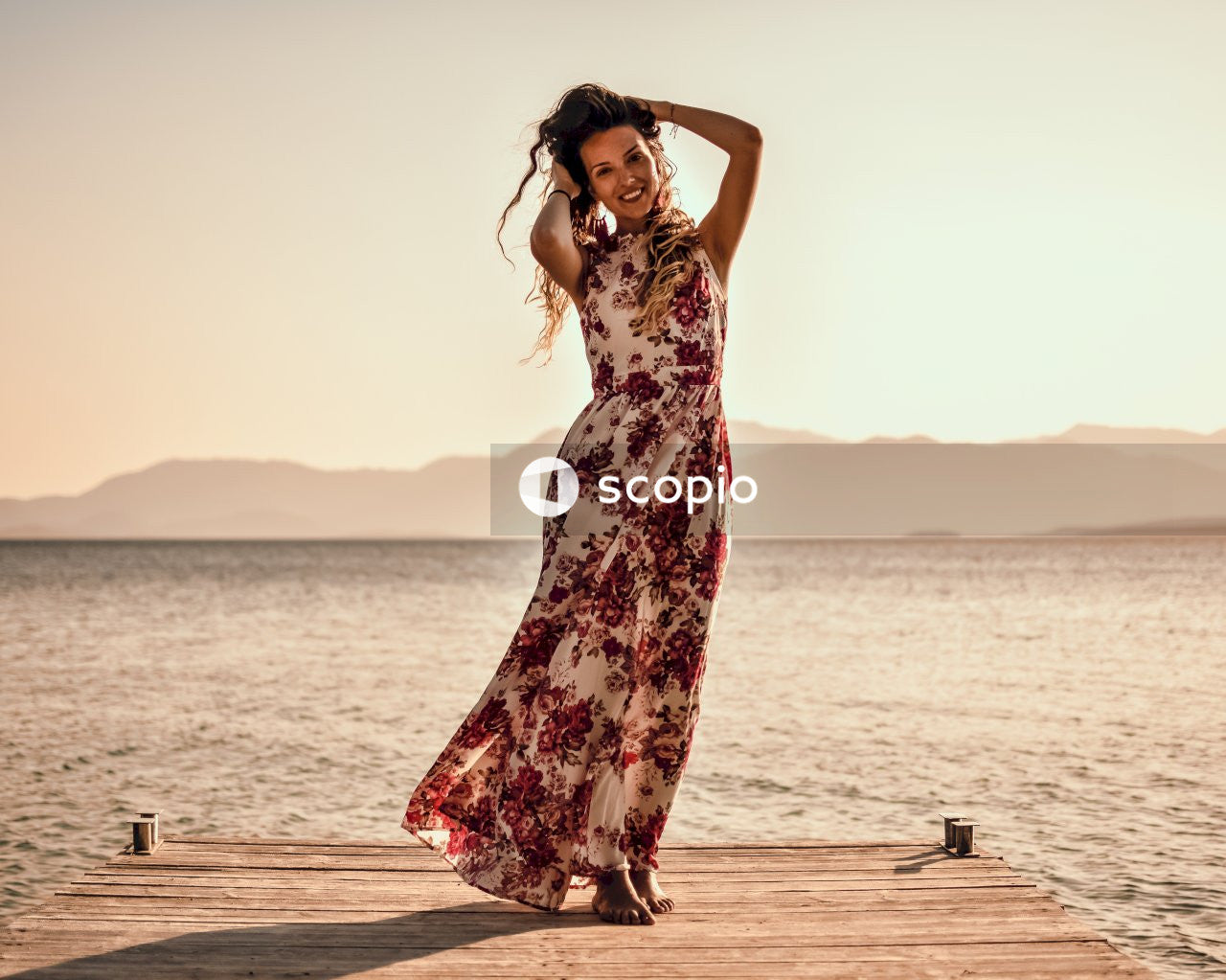 Woman in black and red floral dress standing on brown wooden dock during sunset