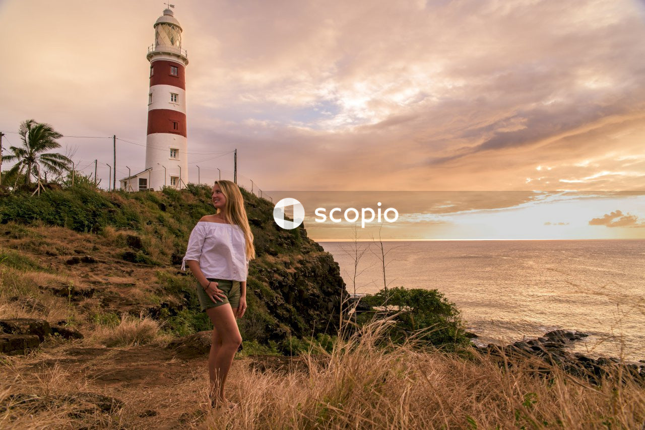 Woman in white shirt and white shorts standing on green grass near white and red lighthouse