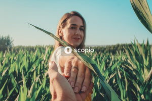 Woman holding green corn plant