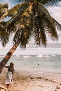 Woman under palm tree on shore