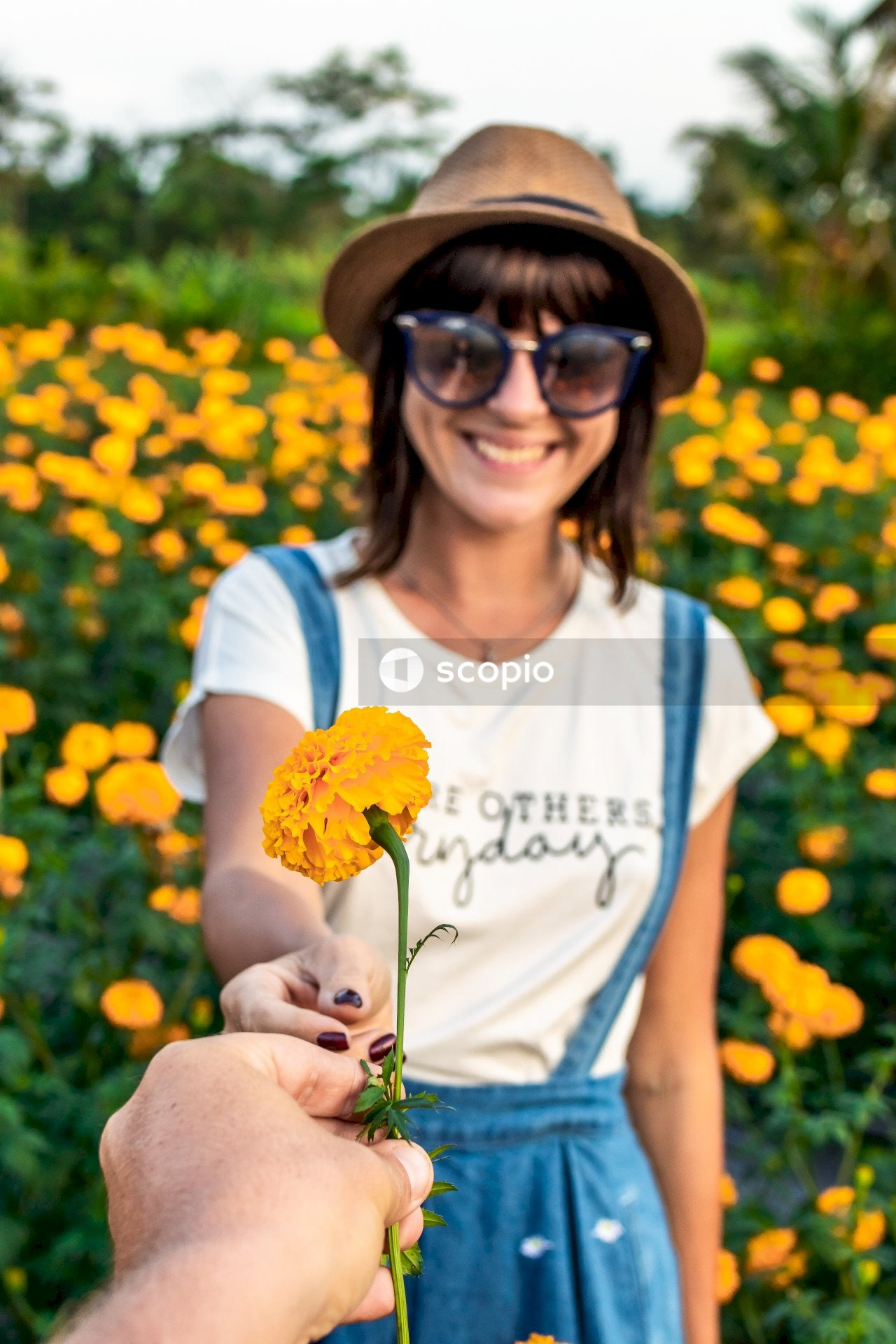 Person giving yellow marigold flower to a woman with brown hat and sunglasses selective-focus