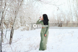 Woman in green coat standing on snow covered ground
