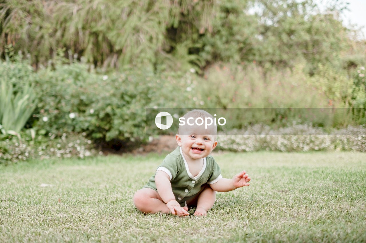 Baby in green shirt sitting on green grass field