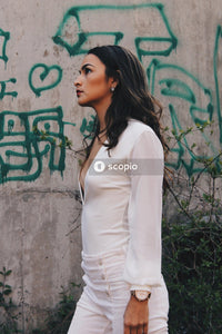 Woman in white long sleeve shirt standing beside wall