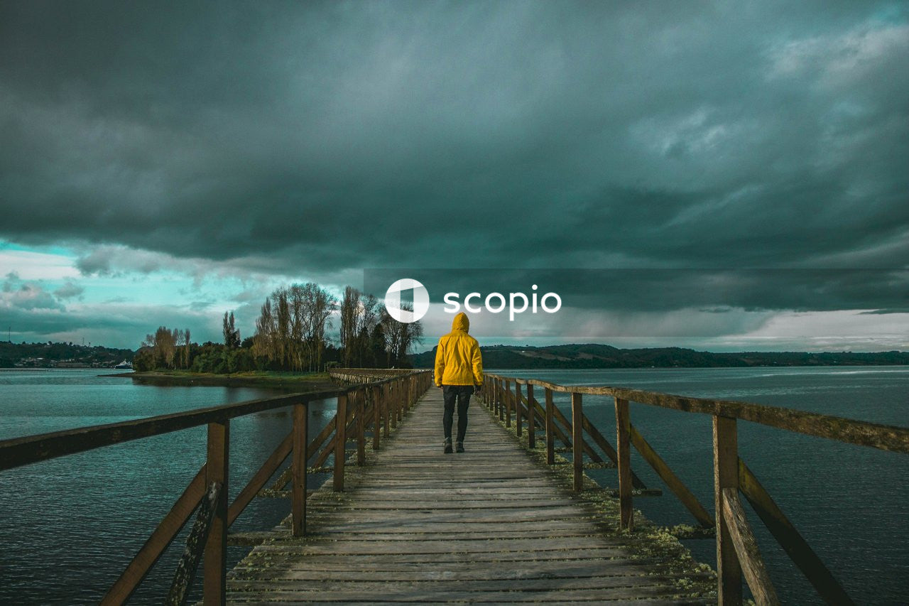 Woman in yellow hoodie standing on wooden dock